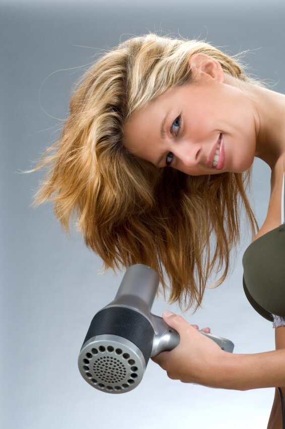 Woman blow drying her hair upside down to get more volume
