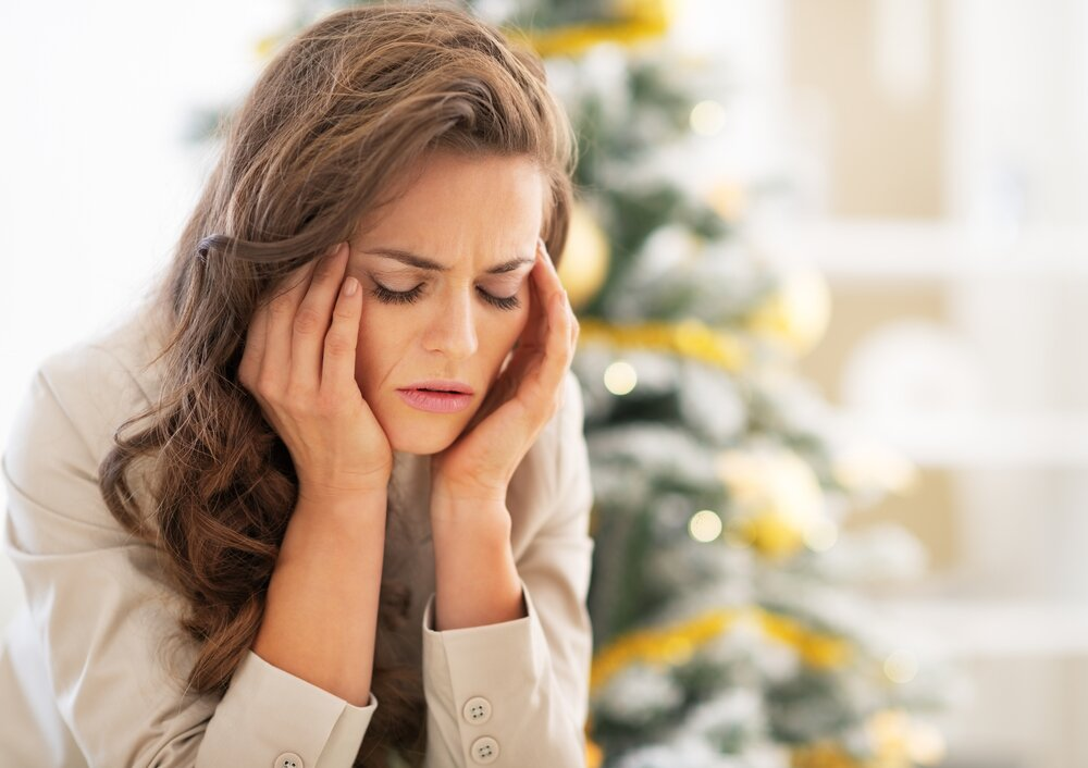 Image of a young woman stressed out with a christmas tree in the background.