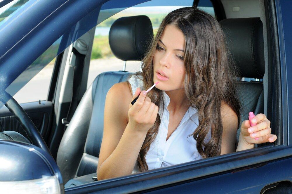 Woman applying lip gloss in a car.