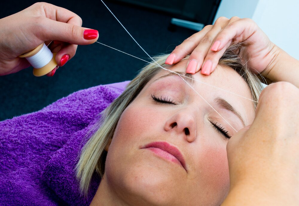Woman getting her eyebrows threaded in a salon.