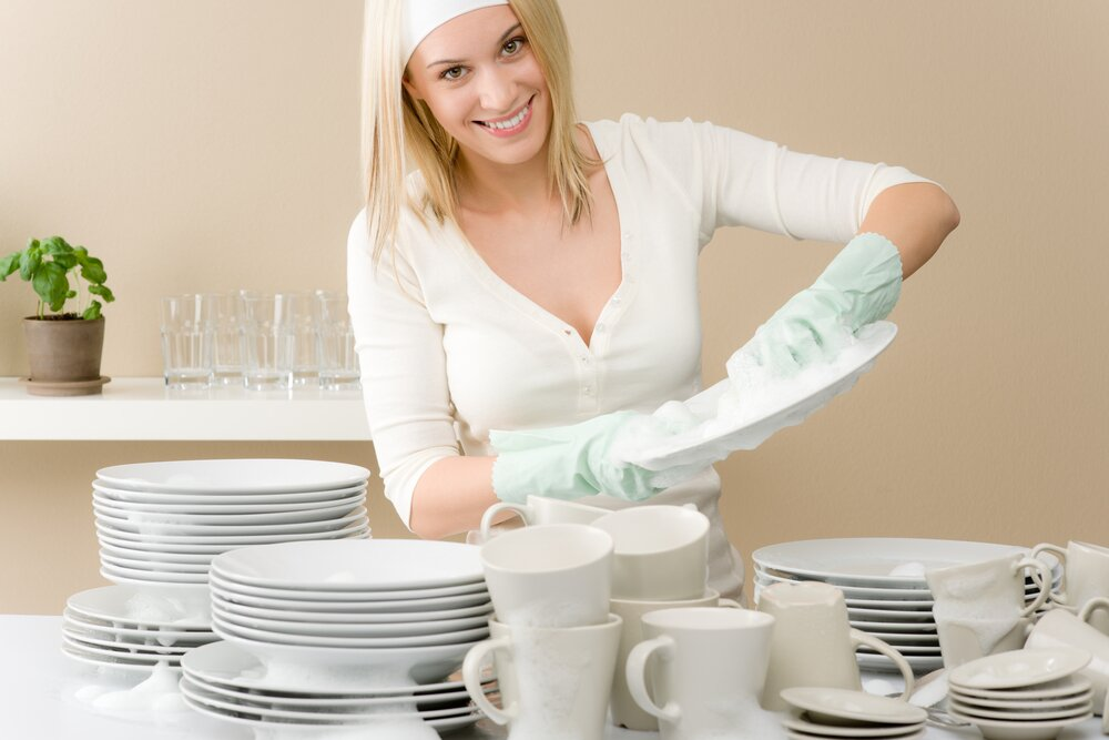 Woman wearing white clothes washing dishes.