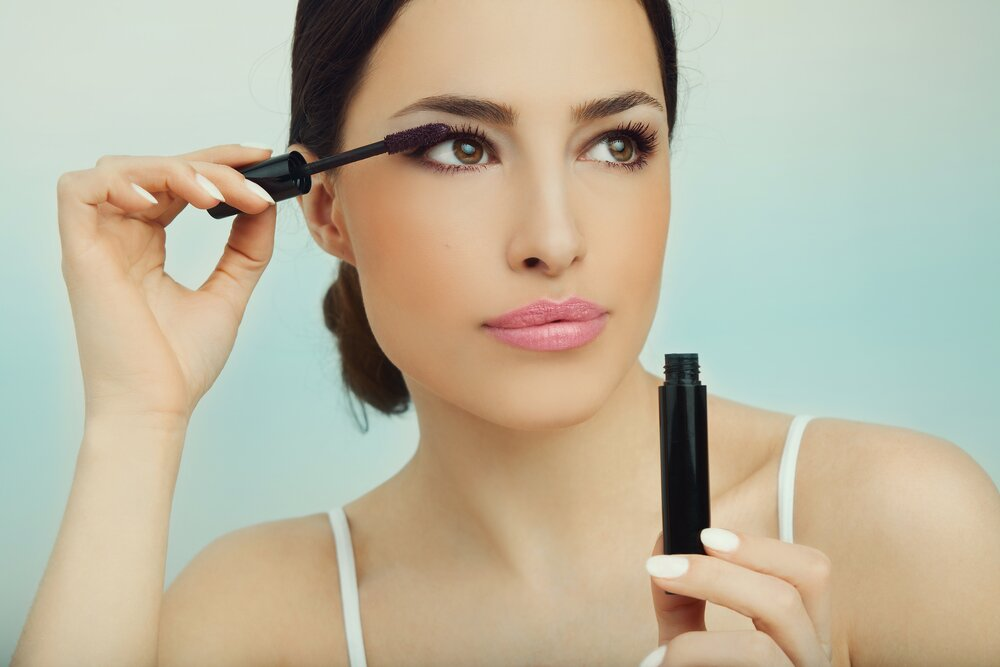 Woman applying some mascara on her eyes.