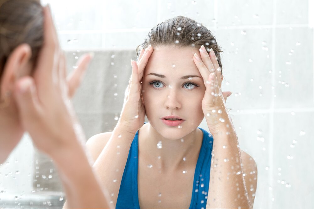 Woman cleansing her face in the morning.