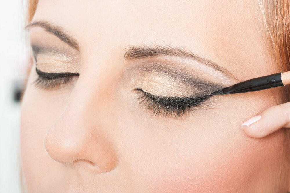 Woman applying an eyeliner.