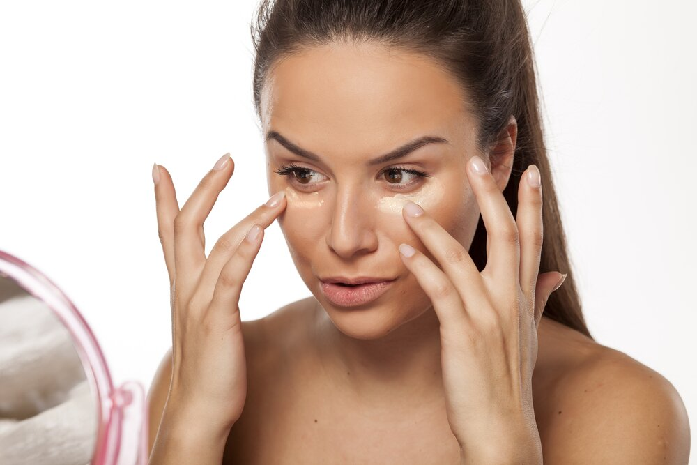 Woman applying a primer on her face.