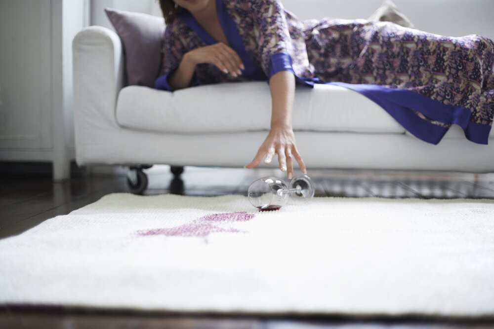 Woman picking up a wine glass after spilling red wine on the rug.