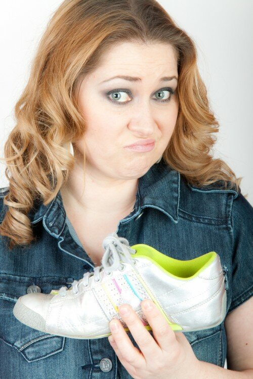 Woman holding smelly sneakers