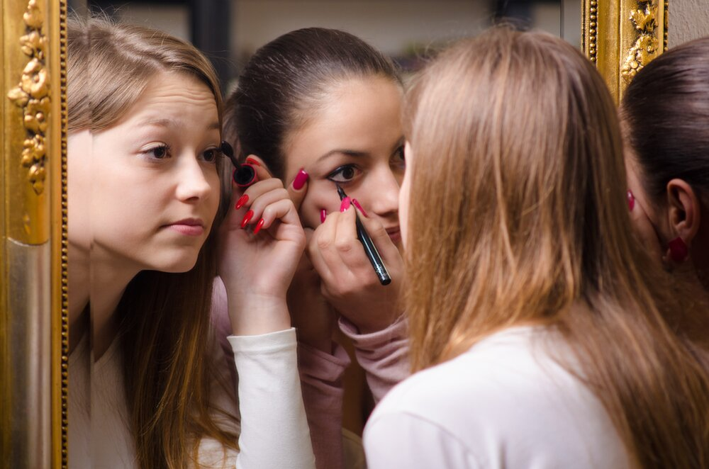 Mother and teen daughter applying makeup