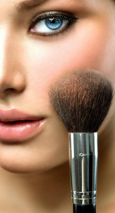 Woman applying blush.