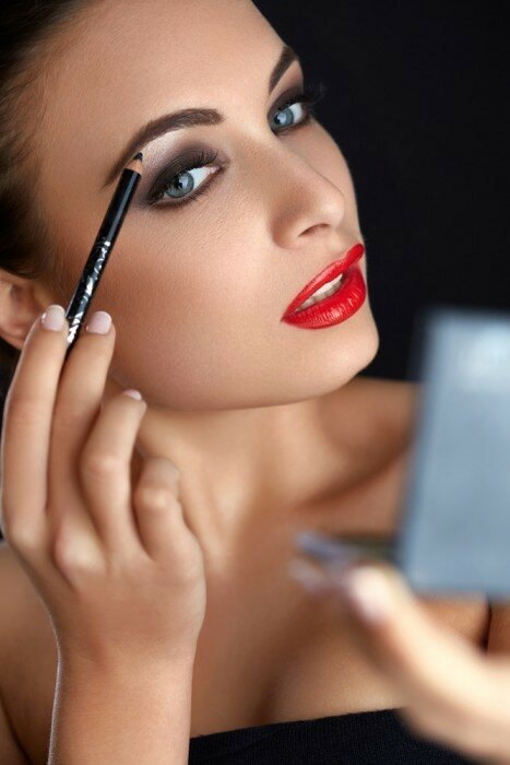 Woman using a brow pencil.