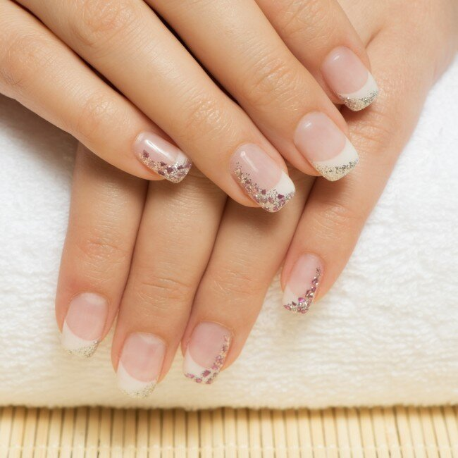 Woman with a glittery French manicure.