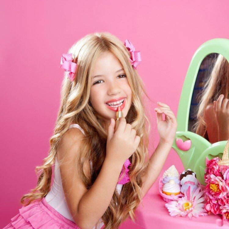 Young girl applying makeup.