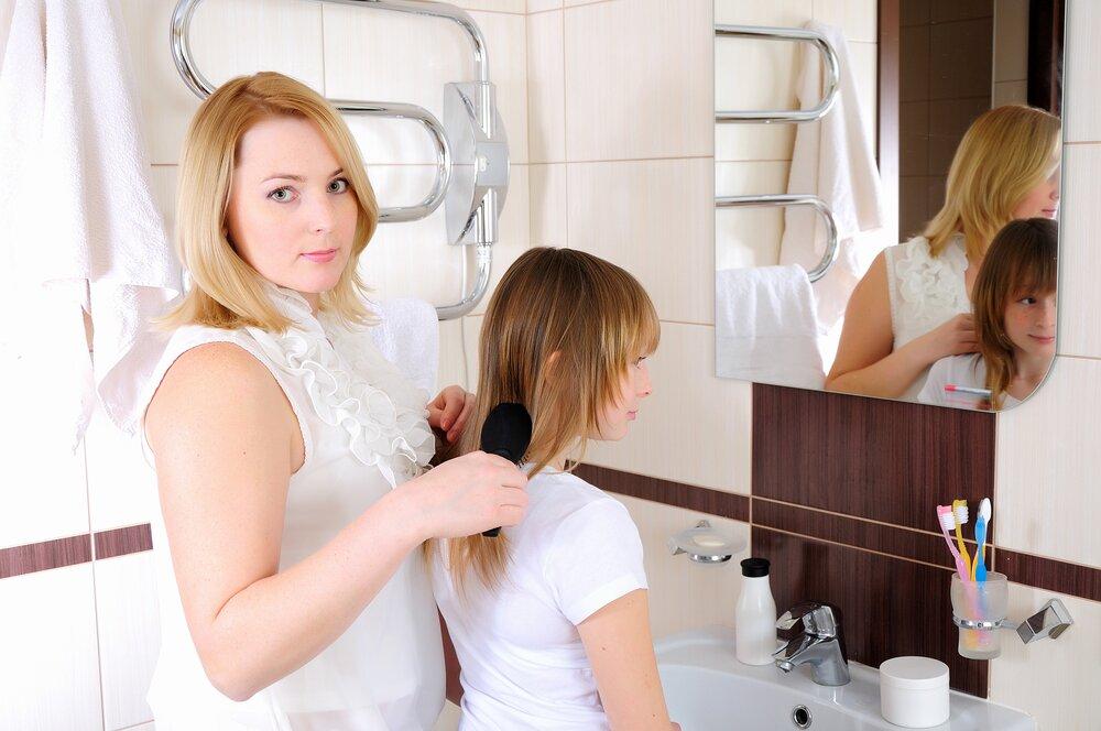 Mother brushing her daughter's hair.