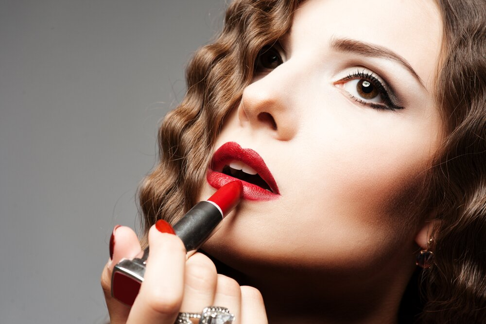 Young girl applying red lipstick.