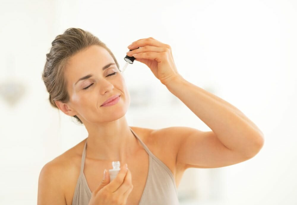 Smiling woman applying face serum