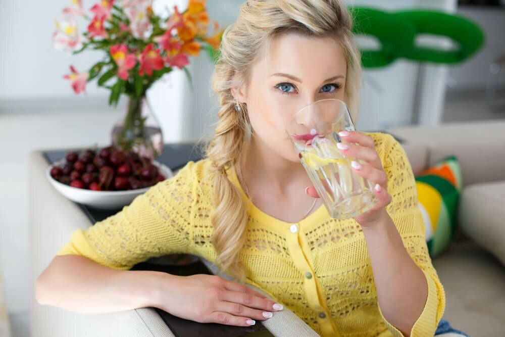 Woman in yellow shirt drinking a glass of water